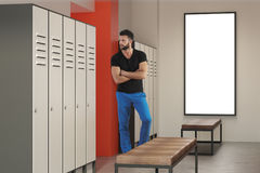 Man in locker room with poster Stock Photo