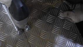 Man locksmith i cuts shiny iron sheet with an electric jigsaw. Close-up.  stock footage