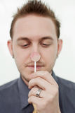 Man with Lollypop. Strange young man holding pink lollypop up to his face Royalty Free Stock Photos