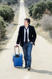 Man in Lonely Road with Suitcase. Handsome man walking in a lonely road with suitcase stock photo