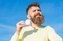 Man with long beard enjoy coffee. Man with beard and mustache on smiling face drinks coffee, blue sky background royalty free stock images