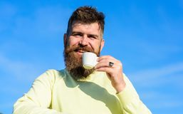 Man with long beard enjoy coffee. Coffee taster concept. Man with beard and mustache on smiling face drinks coffee, blue. Sky background, defocused. Bearded man Stock Photography
