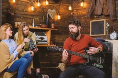 Man with long beard enjoying music. Musician with calm, concentrated face playing for his wife and daughter. Mom helping royalty free stock images