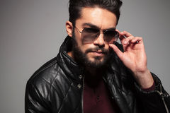 Man with long beard fixing or putting on his sunglasses. Closeup picture of a young man with long beard fixing or putting on his sunglasses Royalty Free Stock Photos