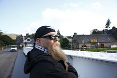 Man with long beard, glasses and headscarf, stands thoughtfully in the sluice gate in the Caledonian Canal. Man with long beard, glasses and headscarf, stands stock image