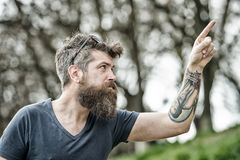 Man with long beard and mustache pointing upwards with finger, defocused background. Guy looks cool with stylish beard. And haircut. Barbershop concept. Hipster Stock Photography
