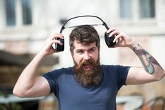 Man with long beard and mustache puts wireless headphones on head, defocused urban background. Hipster with headphones. On shouting face listening music while Royalty Free Stock Photography