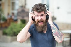 Man with long beard and mustache with wireless headphones on head, defocused urban background. Hipster with headphones. On happy face listening music while Stock Photos
