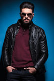 Man with long beard posing with his hands in pockets. Young relaxed man with long beard wearing a leather jacket and sunglasses is posing with his hands in Stock Images
