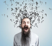 Man with long beard and question marks, gray wall Royalty Free Stock Photo