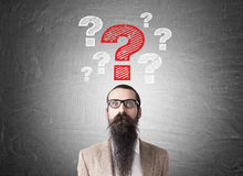 Man with long beard and question marks Royalty Free Stock Photo
