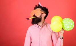 Man with long beard on red background. Bearded man in huge glasses with party whistle, celebration concept. Crazy man. With trimmed beard having fun. Perfomer Royalty Free Stock Photos