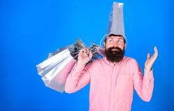 Man with long beard and silver bag on head having fun. Hipster with stylish beard doing shopping, fashion and sales. Concept. Bearded man in pink shirt with royalty free stock photography