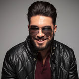 Man with long beard smiling to the camera. While wearing sunglasses and leather jacket Royalty Free Stock Photos