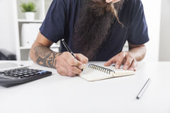 Man with long beard is taking notes Stock Photos