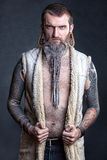 A man with a long beard. A man with a long beard and tunnels in the ears with tattoos stock photos
