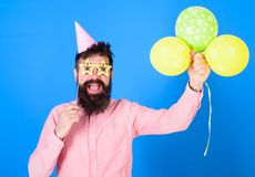 Man with long beard wearing birthday cap having fun with bright balloons. Art perfomer enterteining guests at children. Event. Bearded man with paper party Royalty Free Stock Photography