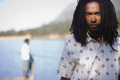 Man, with long dreadlocks, standing beside lake, front view, portrait, focus on foreground Stock Photos