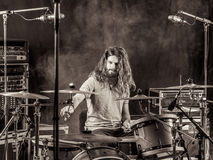 Man with long hair playing drums. Photo of a young male drummer with long hair playing his drum set Royalty Free Stock Photos