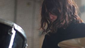 A man with long hair playing drums at repetition. Mid shot