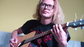 A man plays an acoustic guitar, fingering the frets of a musical intrusion. A man with long hair plays an acoustic guitar, fingers his fingers along the frets of stock footage
