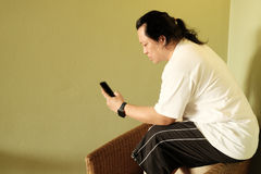Man with long hair reading and using smartphone Royalty Free Stock Photography