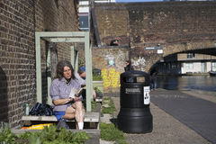 A man with long hair in shorts reading a book, sitting on a bench in the park. LONDON - August 27, 2016: A old man with long hair in shorts reading a book royalty free stock images
