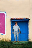 Man With Long Hair Standing Adobe Building Doorway. A man stands in a doorway of an old adobe building. The male has long hair and there is copy space above for Royalty Free Stock Images