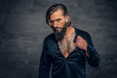 A man with long hair and tattoos on his chest and arms dressed i. Studio portrait of bearded male with long hair and tattoos on his chest and arms dressed in a royalty free stock image