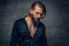 A man with long hair and tattoos on his chest dressed in a black. Studio portrait of bearded male with long hair and tattoos on his chest dressed in a black royalty free stock photography