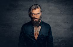 A man with long hair and tattoos on his chest dressed in a black. Studio portrait of bearded male with long hair and tattoos on his chest dressed in a black stock photos