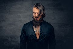 A man with long hair and tattoos on his chest dressed in a black. Studio portrait of bearded male with long hair and tattoos on his chest dressed in a black royalty free stock photos