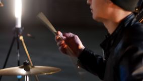 A man with long hair twisting the drumstick between his fingers and gives it to the drummer. Mid shot