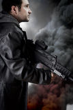 Man with long leather jacket and assault rifle Royalty Free Stock Photography