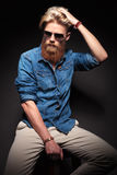 Man with long red beard sitting and fixing his hair Stock Photo