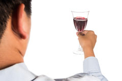 Man in long sleeve shirt toasting red wine in crystal glass.  Royalty Free Stock Photography