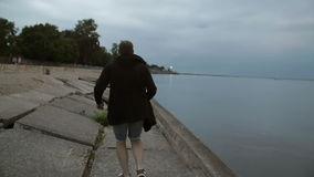 Man in a long sweater running along the beach. Water, trees, moon at the background, slow mo, backview, steadicam shot stock footage