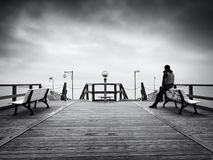 Man on long touristic mole, autumn cold morning. Tourist at handrail. Wet wooden board, constrution above smooth sea royalty free stock image