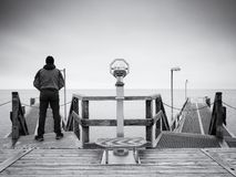 Man on long touristic mole, autumn cold morning. Tourist at handrail. Wet wooden board, constrution above smooth sea royalty free stock photo