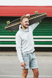 Man with longboard on shoulder Stock Image