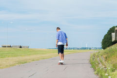 Man with longboard or skateboard riding on road Stock Images