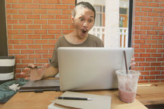 A man look to laptop computer surprised,Shocked Asian man with h. Is work laptop computer,pen mouse and note book on table in coffee shop Stock Photos