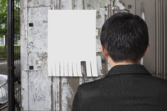 Man look at white paper on noticeboard Royalty Free Stock Images