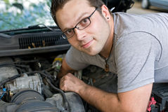 Man Lookging Up. Man looking up as he reaches to change the spark plugs in his car royalty free stock images