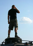 Man is looking. Man standing on a spare wheel on the roof of an SUV Stock Image