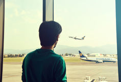 Man looking at an airplane taking flight from the airport waiting area, Bergamo, Italy Royalty Free Stock Photo