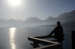 Man looking at Annecy lake and mountains Royalty Free Stock Images