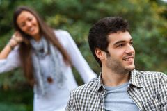 Man looking aside with girlfriend in background. Royalty Free Stock Photo