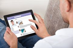 Free Man Looking At Personal Profiles On A Tablet Royalty Free Stock Photos - 43861628