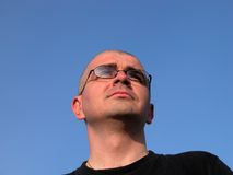 Man looking away. Bald man head with glasses looking away over the blue sky Royalty Free Stock Photo